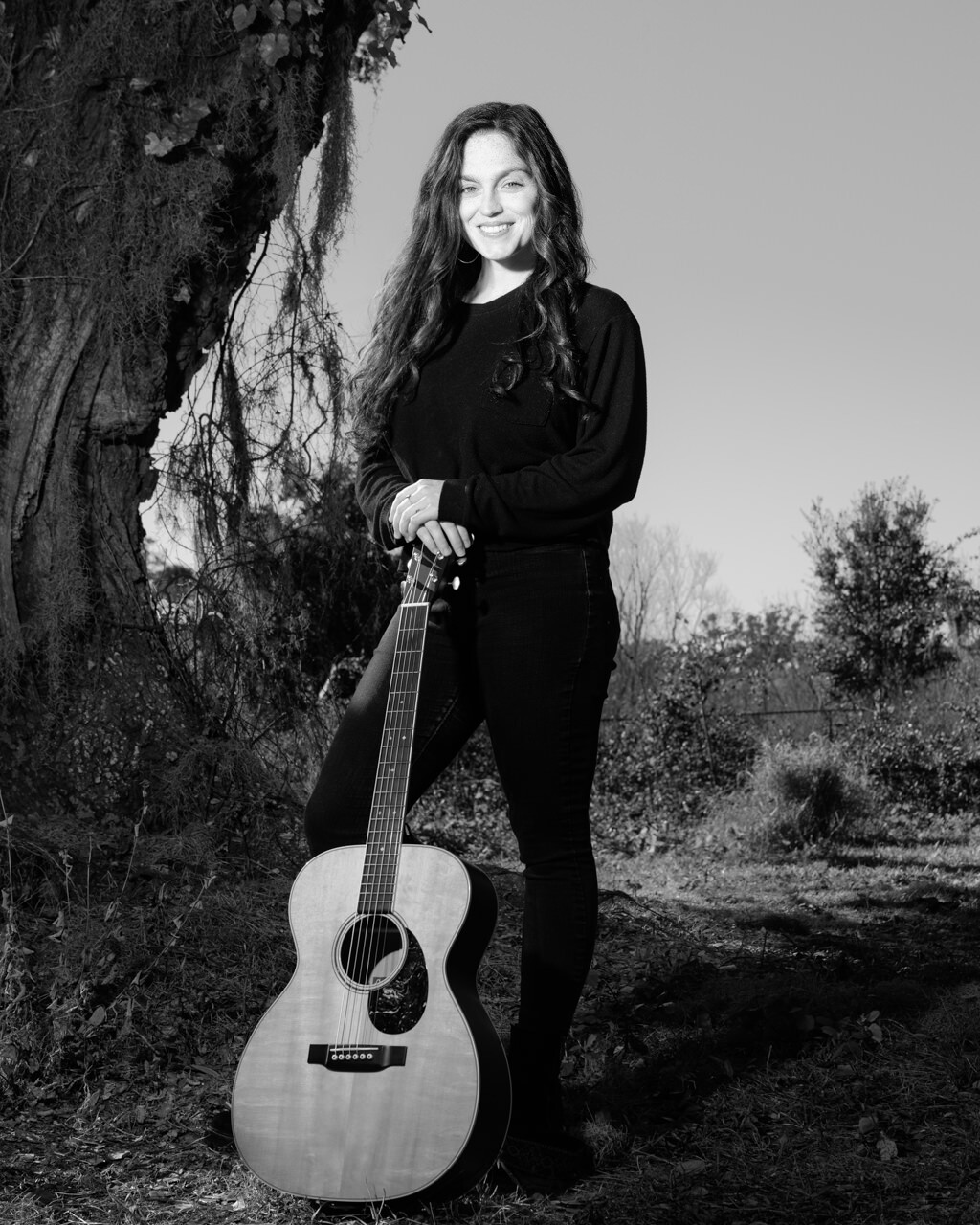 Layla Brisbois singer-songwriter based in orlando posing with her guitar in black and white