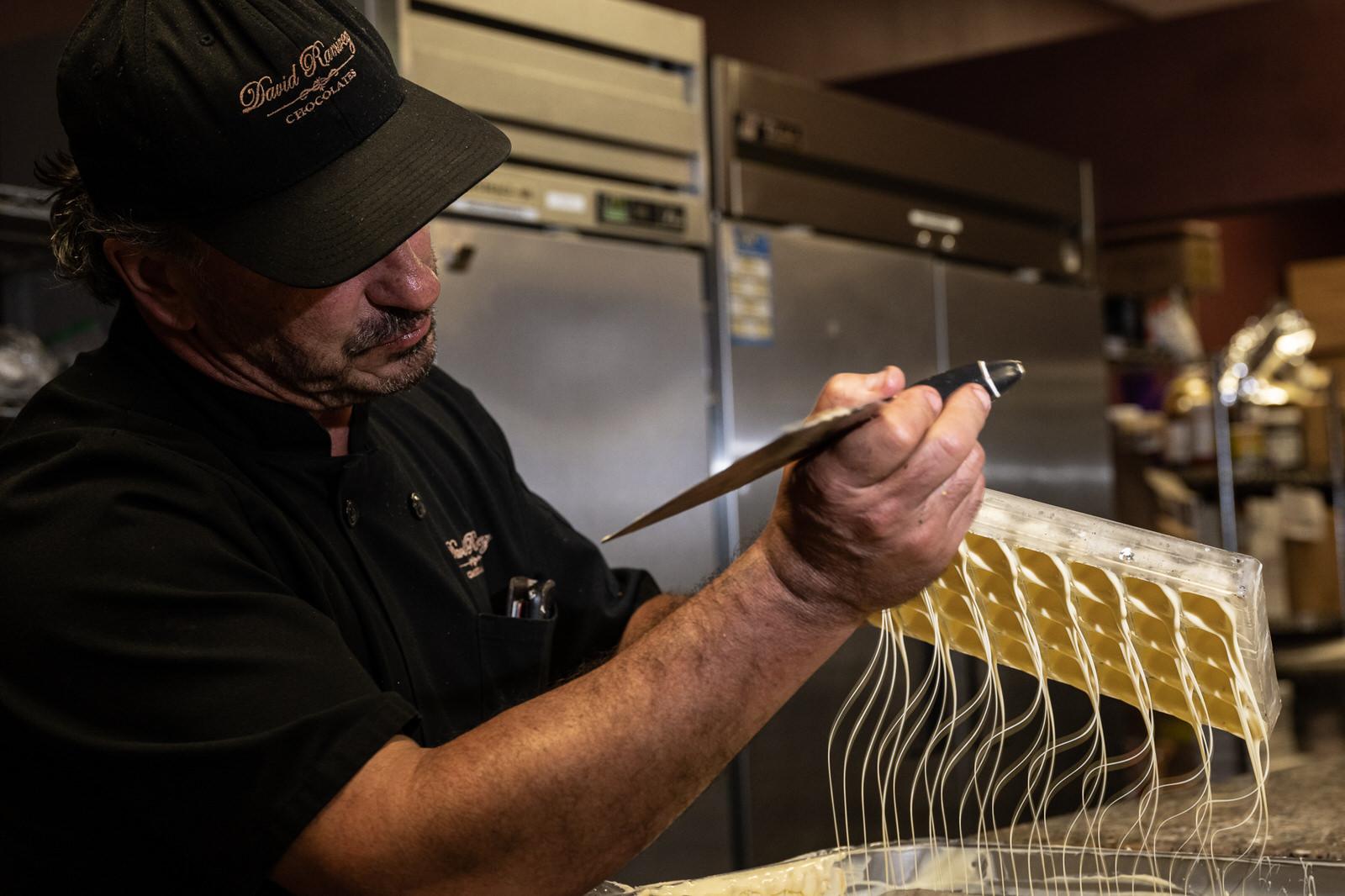 David Ramirez lines the chocolate molds with white chocolate