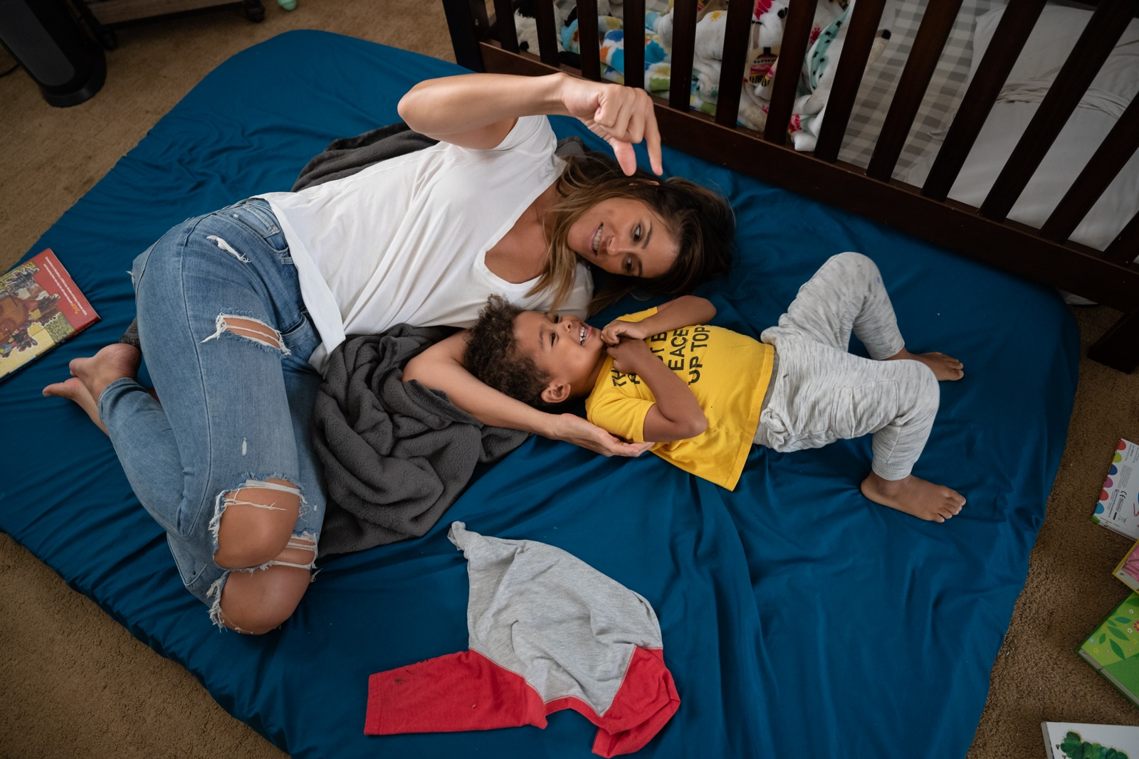 mom plays with her son on his bedroom floor