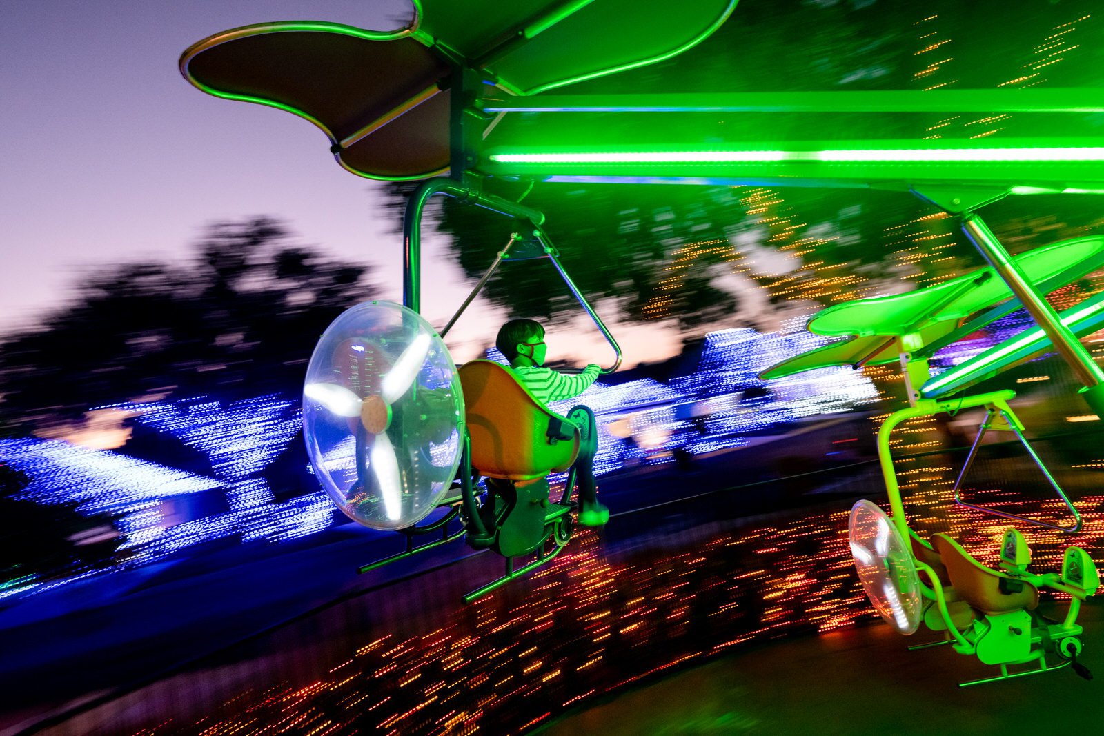 boy takes a ride while enjoying the Christmas lights at Give Kids the World