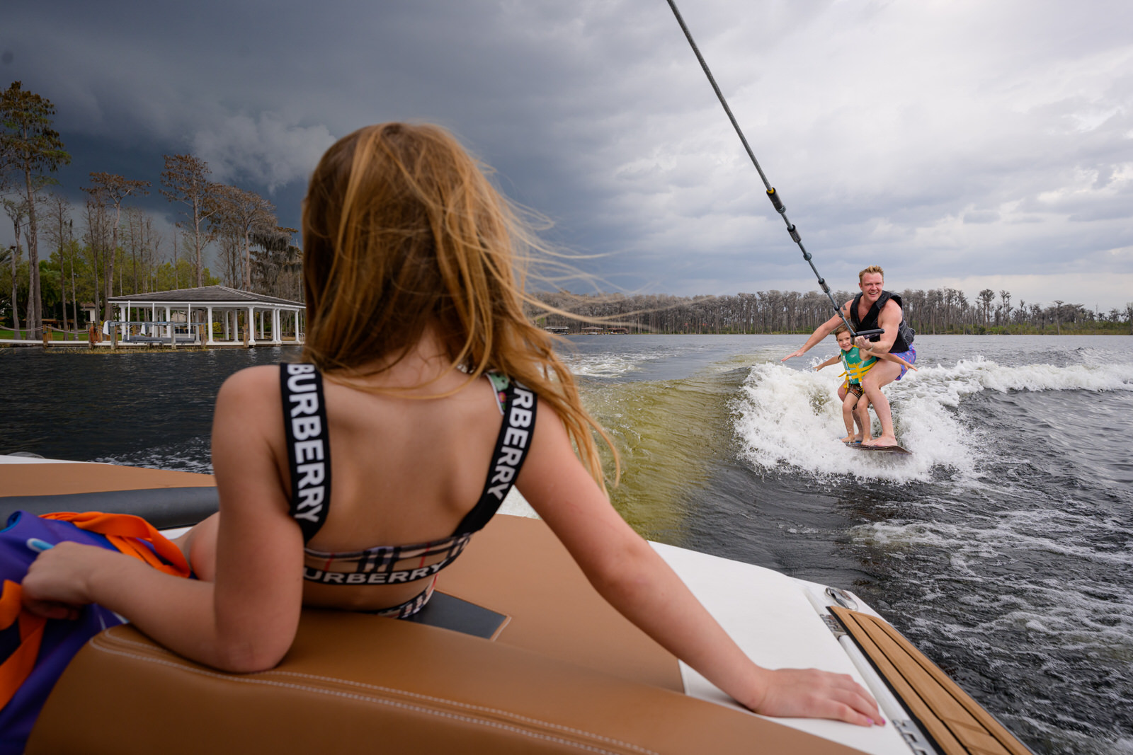 daughter watches her brother and dad wakeboarding
