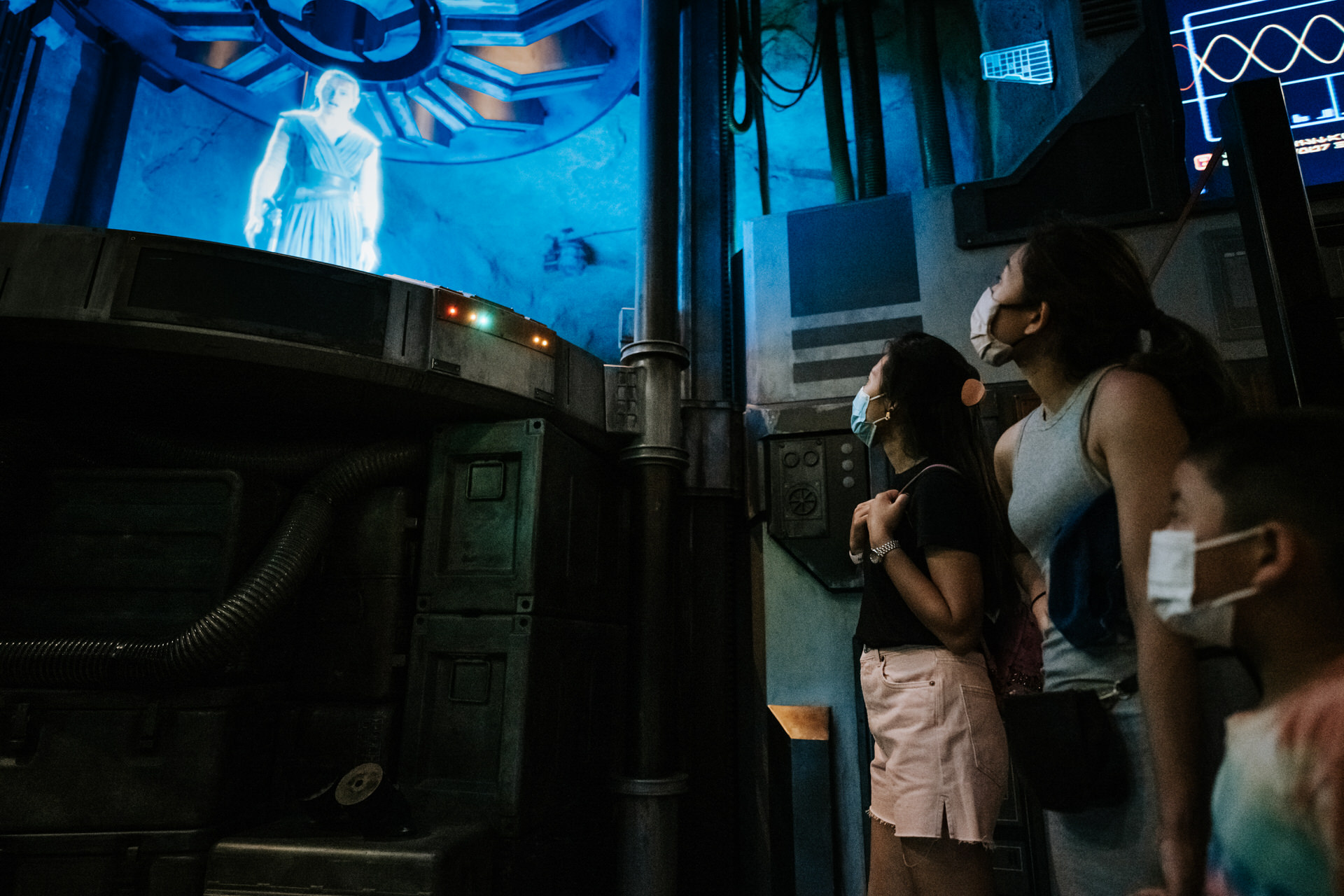 family watches transmission from Rey at Rise of the Resistance