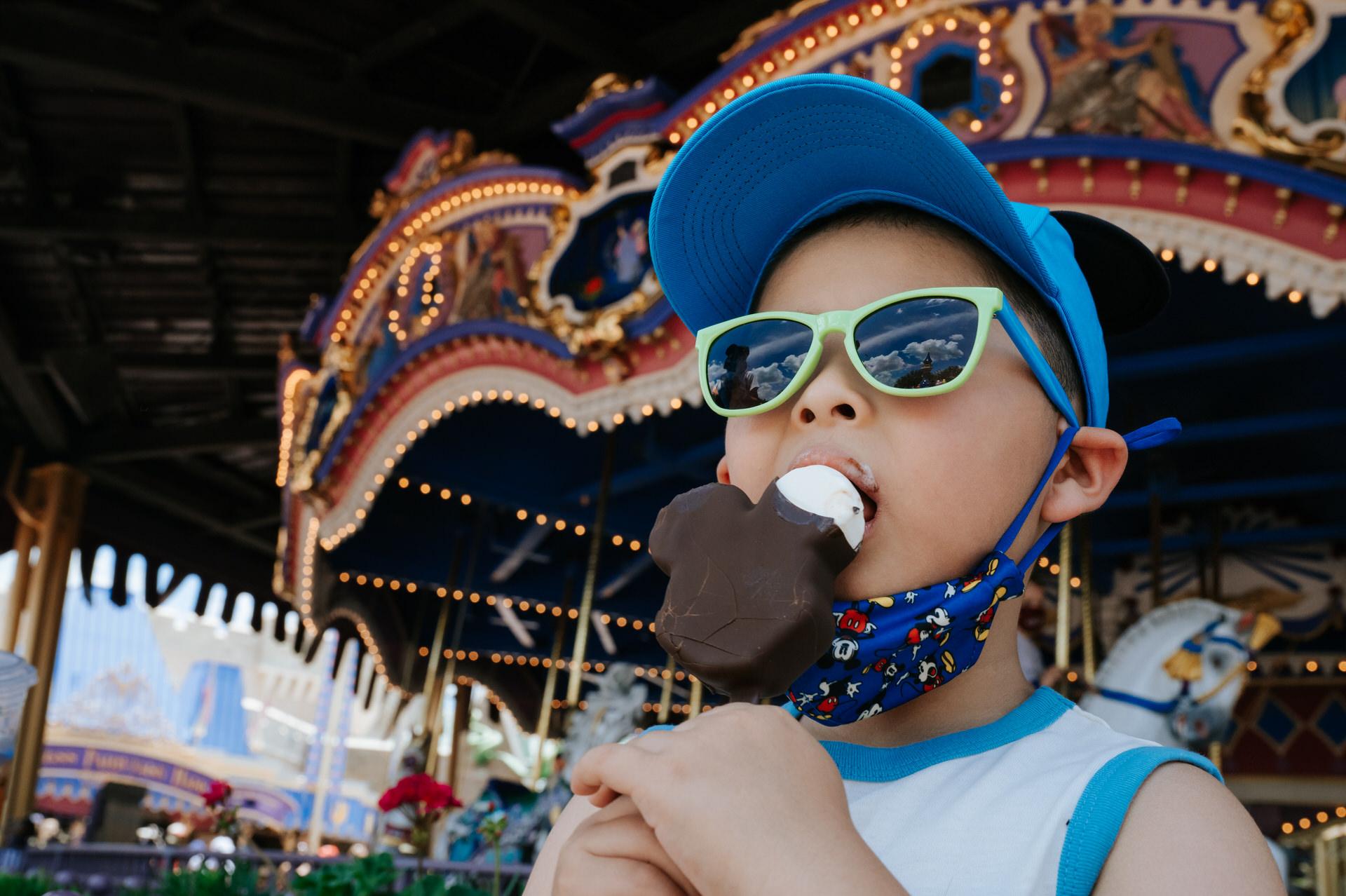 boys enjoys a mickey ice cream bar while waiting for carousel